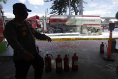 A police officer guards a Pertamina fuel station on Jl. MT Haryono in South Jakarta after a fuel tanker had caught fire on Dec. 1. Fuel station workers managed to put out the flames. JP/Wendra Ajistyatama