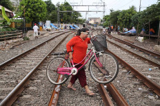 A woman carries her bicycle across railway tracks in Kramat, Central Jakarta, on Nov. 30. Because railway lines are not separated from residential areas, people often cross the tracks, thereby endangering their lives. JP/P.J. Leo