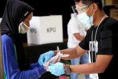 A poll worker (right) helps a woman put on a plastic glove before she casts her ballot at a polling station in Tapos, Depok, West Java, on Dec. 9. Poll workers enforced strict health protocols on voting day for the Depok mayoral election, requiring voters to wear gloves and face masks, among other precautions. JP/P.J. Leo