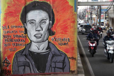 Motorists ride past a mural portraying missing activist and poet Wiji Thukul on Jl. Raya Ciledug, Cipulir, South Jakarta, on Dec. 10, coinciding with the commemoration of International Human Rights Day. JP/Seto Wardhana