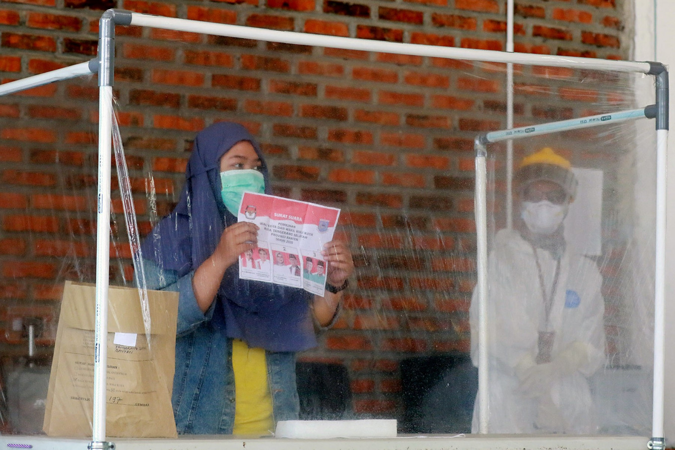 A COVID-19 patient (left) casts her ballot as a health officer wearing personal protective gear looks on at a COVID-19 isolation facility that was treating 49 voters in South Tangerang, Banten, on Dec. 9. JP/Dhoni Setiawan