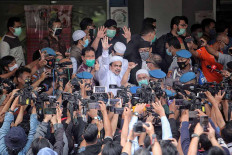 Islam Defenders Front (FPI) leader Rizieq Shihab arrives at the Jakarta Police headquarters in Jakarta on Dec. 12. Rizieq was summoned by the police for allegedly breaching health protocols by holding crowded events at his house and at the group's headquarters in Petamburan, Central Jakarta, last month. JP/Seto Wardhana.