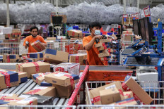 Employees sort out goods at a Lazada warehouse in Cimanggis, West Java, on Dec. 17. During Lazada's three-day national online shopping (Garbolnas) held on Dec. 12-14, the online shop saw a 100 percent increase in sales compared with 2019. Bank Indonesia (BI) recorded Rp 180.74 trillion (US$ 12.8 billion) in e-commerce transactions as of September, lower than the 2019 figure of Rp 201 trillion. JP/Seto Wardhana