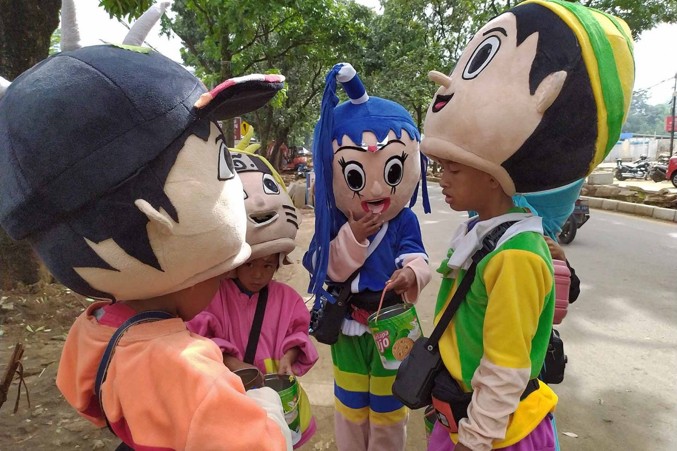 Children wearing costumes of various cartoon characters work as street singers to collect money from passersby in Cibinong, Bogor regency, West Java, on Dec. 14. They said they went out busking after attending their online classes. JP/P.J. Leo