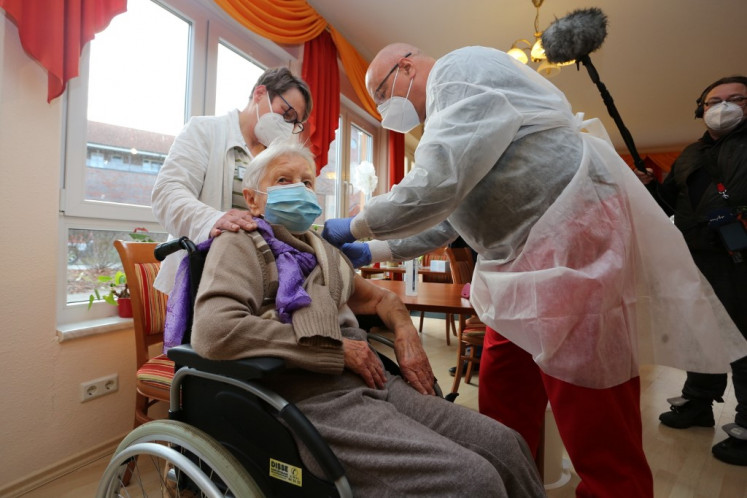 Edith Kwoizalla, 101 years old, receives the first vaccination against the novel coronavirus COVID-19 by Pfizer and BioNTech from Doctor  Bernhard Ellendt (R) in a senior care facility in Halberstadt (Seniorenzentrum Krueger), central northern Germany, on December 26, 2020. - The European Union began a vaccine rollout, even as countries in the bloc were forced back into lockdown by a new strain of the virus, believed to be more infectious, that continues to spread from Britain. The pandemic has claimed more than 1.7 million lives and is still running rampant in much of the world, but the recent launching of innoculation campaigns has boosted hopes that 2021 could bring a respite.