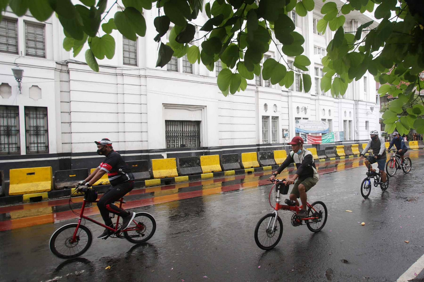 Cyclists pass through Kota Tua, West Jakarta, on Dec. 20. The city administration has limited the number of motorized vehicles that are permitted in the heritage tourist site during a low-emission zone trial from Dec. 18 to Dec. 23. JP/Wendra Ajistyatama