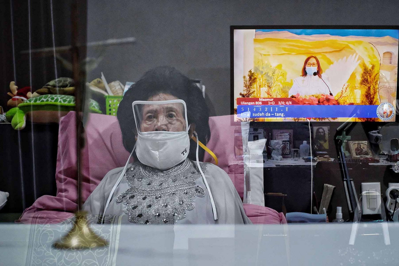 Thutty Soekotjo, 92, watches an online Holy Mass in South Tangerang, Banten, on Dec. 24. Most Christians attended online masses as churches implemented strict health protocol, including restricting the age and limiting numbers of congregants, to curb COVID-19 transmission during Christmas. JP/Seto Wardhana