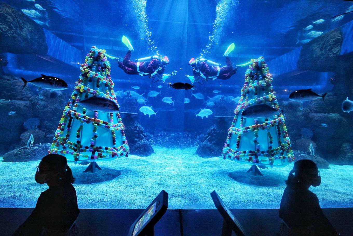 Visitors look at a performance by divers in Santa Claus costumes at the Jakarta Aquarium and Safari, at Neo Soho Mall, in Grogol, West Jakarta on Dec. 22, 2020. Thousands of aquatic and terrestrial animals are on display at the tourist spot, which is open to the public under tight enforcement of health protocol. JP/Seto Wardhana