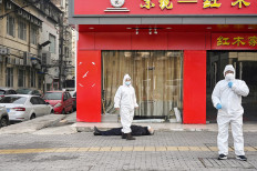 This photo taken on January 30, 2020 shows officials in protective suits checking on an elderly man wearing a facemask who collapsed and died on a street near a hospital in Wuhan. - AFP journalists saw the body on January 30, not long before an emergency vehicle arrived carrying police and medical staff in full-body protective suits. The World Health Organization declared a global emergency over the new coronavirus, as China reported on January 31 the death toll had climbed to 213 with nearly 10,000 infections. AFP/Hector Retamal