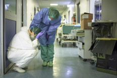 A nurse wearing protective mask and gear comforts another as they change shifts on March 13, 2020 at the Cremona hospital, southeast of Milan, Lombardy, during the country's lockdown aimed at stopping the spread of the COVID-19 (new coronavirus) pandemic. - After weeks of struggle, they're being hailed as heroes. But the Italian healthcare workers are exhausted from their war against the new coronavirus. AFP/Paolo Miranda