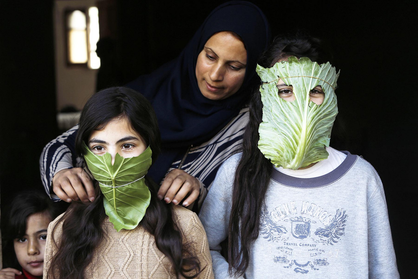 A Palestinian mother entertain her children with makeshift masks made of cabbage as she cooks in Beit Lahia in the northern Gaza Strip on April 16, 2020 amid the coronavirus COVID-19 pandemic. AFP/Mohammed Abed