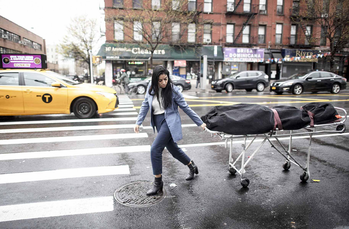 Alisha Narvaez Manager at International Funeral & Cremation Services transports a body to the funeral home on April 24, 2020 in the Harlem neighborhood of New York City. - For many families already in distress, finding a funeral home in New York that will accept the body of a loved one is a headache; in Harlem, International Funeral home tries not to turn anyone away, even if it means being under stress. AFP/Johannes Eisele