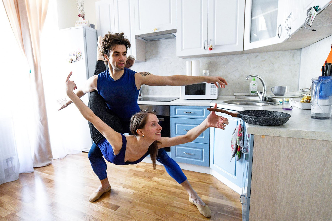 Bolshoi theatre leading soloist Igor Tsvirko and first soloist Margarita Shrainer attend a lesson in the kitchen of their apartment in Moscow on April 29, 2020 during a strict lockdown in Russia to stop the spread of the COVID-19 infection caused by the novel coronavirus. - In the middle of their bedroom, Bolshoi ballet dancers Margarita Shrainer and Igor Tsvirko have placed a linoleum mat and a barre. Since the start of the lockdown, the couple, both soloists in the legendary troupe, have largely used their own initiative to keep up their dance skills at home. AFP/Kirill Kudryavtsev