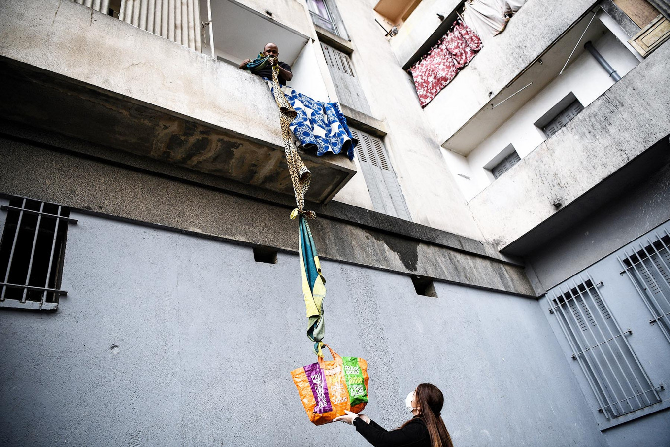 An inhabitant of the residence Maison Blanche (White House residence), composed of 226 mostly unsanitary dwellings, collects food offered by neighbours from his balcony, using a rope made with blankets, on March 31, 2020, in Marseille, southern France, on the fifteenth day of a lockdown aimed at curbing the spread of the COVID-19 (novel coronavirus). AFP/Anne-Christine Poujoulat