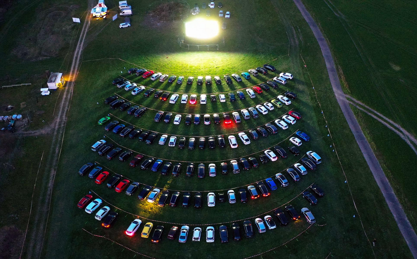 An aerial view shows cinema goers sitting in their cars parked at a drive-in cinema in Marl, western Germany, on April 6, 2020, one of the few entertainments still allowed due to the spread of the novel coronavirus COVID-19. AFP/Ina Fassbender