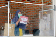 Polls amid pandemic: A COVID-19 patient casts her ballot as a health officer wearing personal protective gear looks on at a COVID-19 isolation facility that was treating 49 voters in South Tangerang city, Banten, on Dec.9. JP/ Dhoni Setiawan