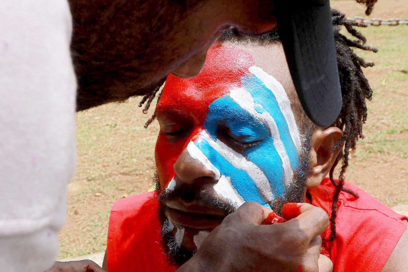 Justice seekers: A Papuan Students Alliance (AMP) member has his face painted with the colors of the Bintang Kejora (Morning Star) flag during a protest on Jl Medan Merdeka Barat, Central Jakarta on Nov. 16. The protesters demanded that the government thoroughly investigate the killing of Papuan pastor Yeremia Zanambani in Intan Jaya, Papua, and withdraw military and police personnel from the country's easternmost province. JP/ Dhoni Setiawan