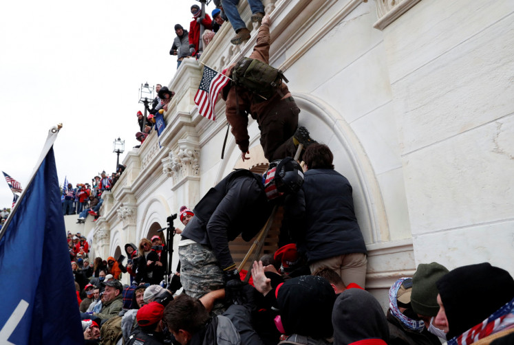Pro-Trump protesters scale a wall as they storm the US Capitol Building, during clashes with Capitol police at a rally to contest the certification of the 2020 U.S. presidential election results by the US Congress, in Washington, U.S, Wednesday