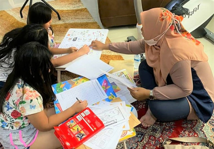 Home visit: A teacher visits the home of her students during the school closures in Lombok, West Nusa Tenggara in November 2020.