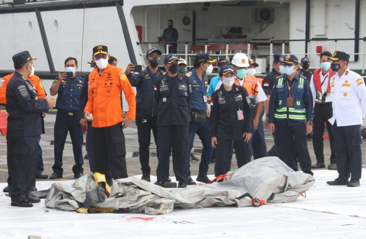 Rescue workers inspect recovered debris at the port in Jakarta on January 10, 2021, during the search operation for Sriwijaya Air flight SJY182 which crashed after takeoff from Jakarta on January 9.