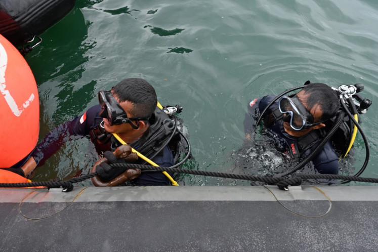 Navy divers prepare to go under during recovery operations for the ill-fated Sriwijaya Air Boeing 737-500 passenger aircraft near Lancang Island on January 10, 2021, following the January 9 crash of flight SJ182 into the Java Sea minutes after takeoff.