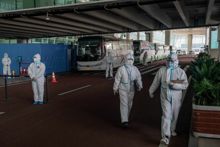 Health workers in personal protection suits stand next to buses at a cordoned-off section at the international arrivals area, where arriving travellers are to be taken into quarantine, at the international airport in Wuhan on January 14, 2021, following the arrival of a World Health Organization (WHO) team investigating the origins of the Covid-19 pandemic.