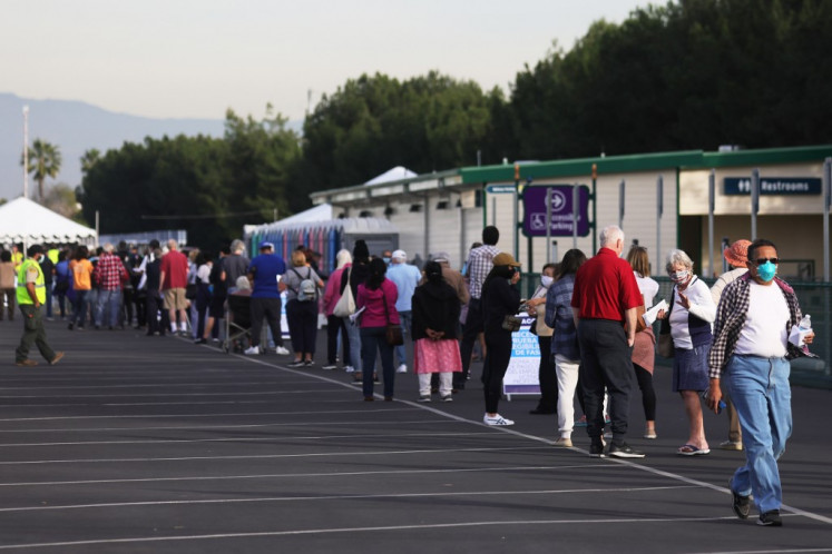 People wait in line to receive the COVID-19 vaccine at a mass vaccination site in a parking lot for Disneyland Resort on January 13, 2021 in Anaheim, California. California announced that effective immediately, all residents 65 or older are eligible to receive the vaccine.