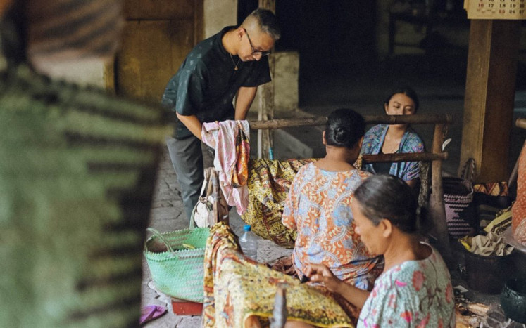 Building a community: Didiet (standing) interacts with batik artisans in Lasem, Central Java. The website provides information on how to connect with fashion-related SMEs and purchase their products.