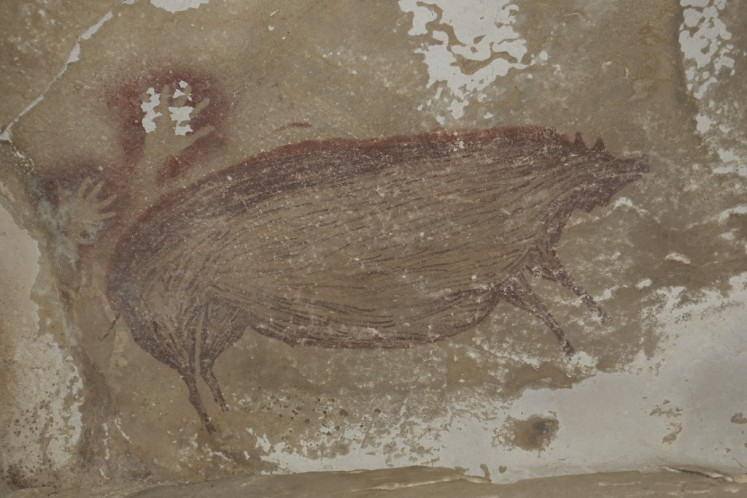 This undated handout photo shows a dated pig painting at Leang Tedongnge in Sulawesi, Indonesia. Archaeologists have discovered the world's oldest known cave painting: a life-sized picture of a wild pig that was made at least 45,500 years ago in Indonesia.