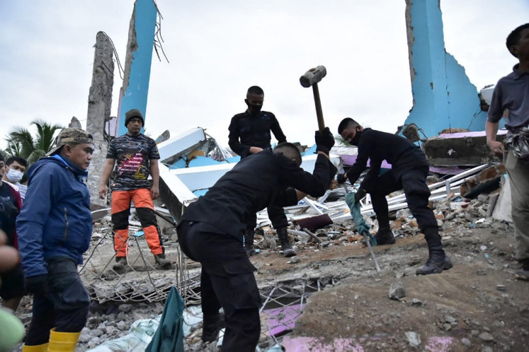 Rescuers search for survivors at the Mitra Manakarra hospital in Mamuju city on January 15, 2021, where as many as 20 patients and staff are trapped beneath the rubble after the hospital was flattened when a 6.2-magnitude earthquake rocked Indonesia's Sulawesi island.