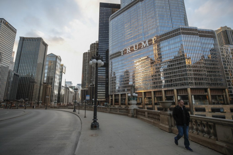 In this file photo taken on March 21, 2020 a man walks by Trump International Hotel and Tower in Chicago, Illinois. Donald Trump shot to prominence with a business empire that bears his name, but after four years of political tumult capped by his supporters' violent attack on the Capitol, the US president's brand stands tarnished, threatening his businesses, experts say.