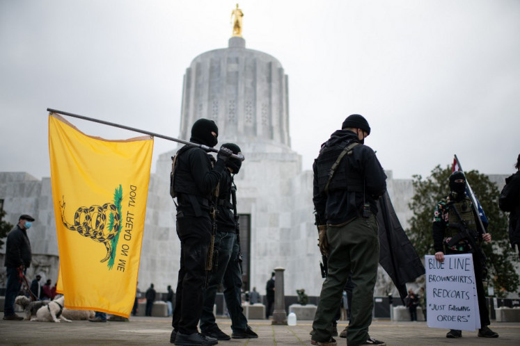 Members of the Boogaloo Boys stand armed in front of the Oregon Sate Capitol building in Salem on January 17, 2021, during a nationwide protest called by anti-government and far-right groups supporting US President Donald Trump and his claim of electoral fraud in the November 3 presidential election. The FBI warned authorities in all 50 states to prepare for armed protests at state capitals in the days leading up to the January 20 presidential inauguration of President-elect Joe Biden.