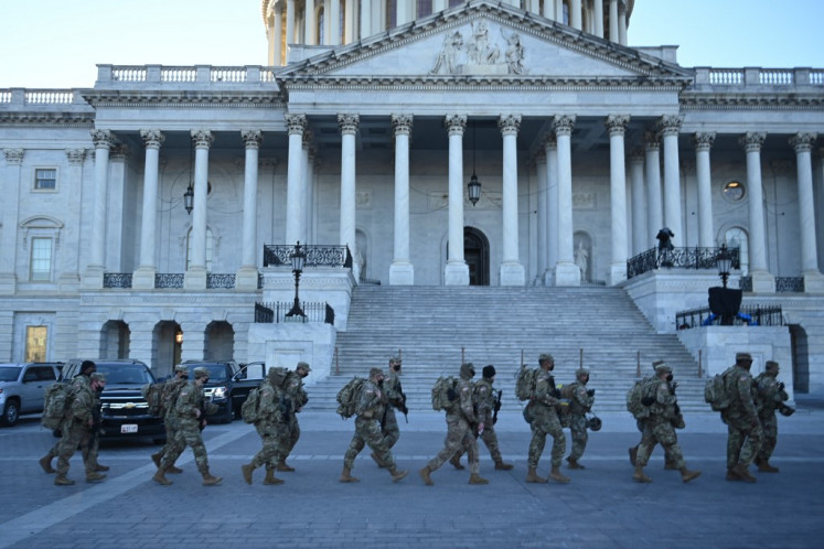Members of the US National Guard walk outside the US Capitol on January 19, 2021 in Washington, DC, ahead of the 59th inaugural ceremony for President-elect Joe Biden and Vice President-elect Kamala Harris.