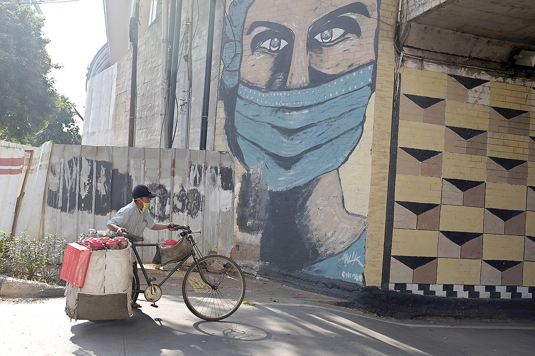 Life goes on: A food vendor pushes his laden bicycle past a coronavirus-themed mural of a health worker in Tebet, South Jakarta on Jan. 9, 2021. The prolonged pandemic does not affect people's spirit to remain active. (Courtesy of JADIGUNAImages/Jerry Adiguna)