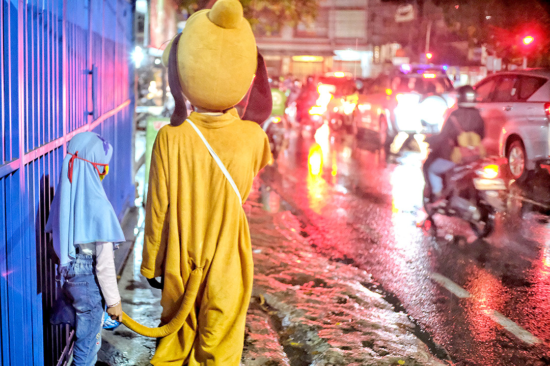Soldiering on: A busker in an animal character costume shelters from the rain with his daughter along a busy street Jakarta on Jan. 26, 2021, in this color-monochrome photomontage. Indonesia reached 1 million COVID-19 cases on that day.(JP/Seto Wardhana)