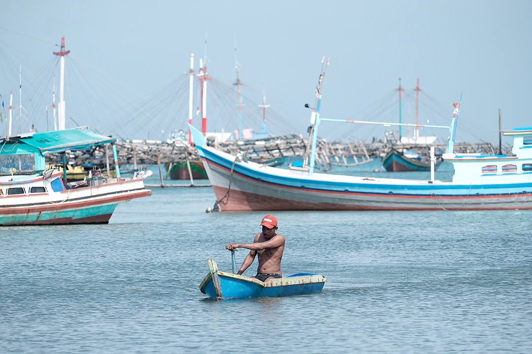 Way back home: After overcoming turbulent waves in the wake of larger ships, we, just like the fisherman here in his dinghy, head home to our lands.