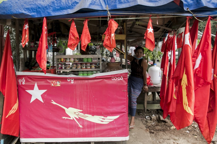 A supporter of the National League of Democracy (NLD) decorates her shop with NLD flags ahead of the reopening of the parliament on February 1 following the November 2020 elections which Aung San Suu Kyi's ruling NLD won in a landslide, in Yangon on January 30, 2021.