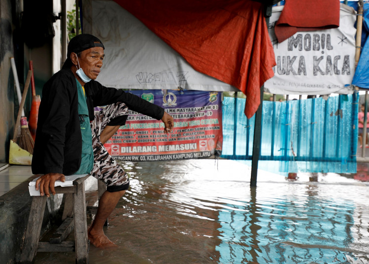 A man sits on a bench in an area affected by floods in Jakarta, Indonesia, February 8, 2021.