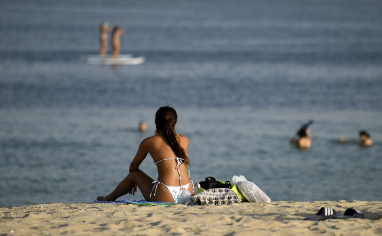 In this file photo taken on July 24, 2020, a woman sunbather sits along a beach as people stand up paddle board in the water in the Gulf emirate of Dubai. In Dubai, known for its luxury haunts and parties, expatriate singles working in the city find the quest for a partner difficult.