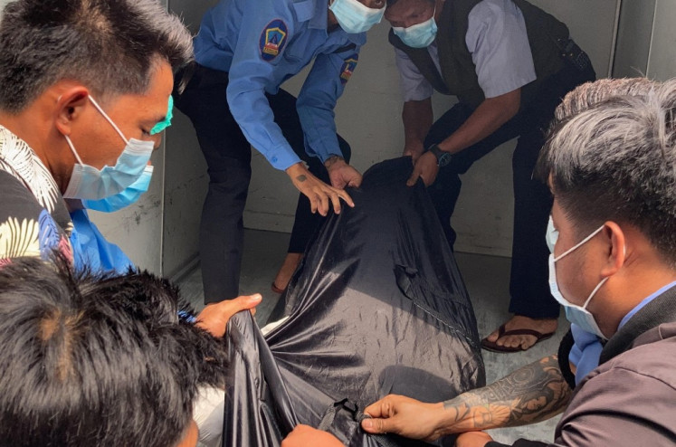 Hospital staff carry a body bag bearing the remains of Mya Thwate Thwate Khaing, a 20-year-old woman who was shot in the head last week during an anti-coup protest in Myanmar's capital Naypyidaw on Feb. 19.
