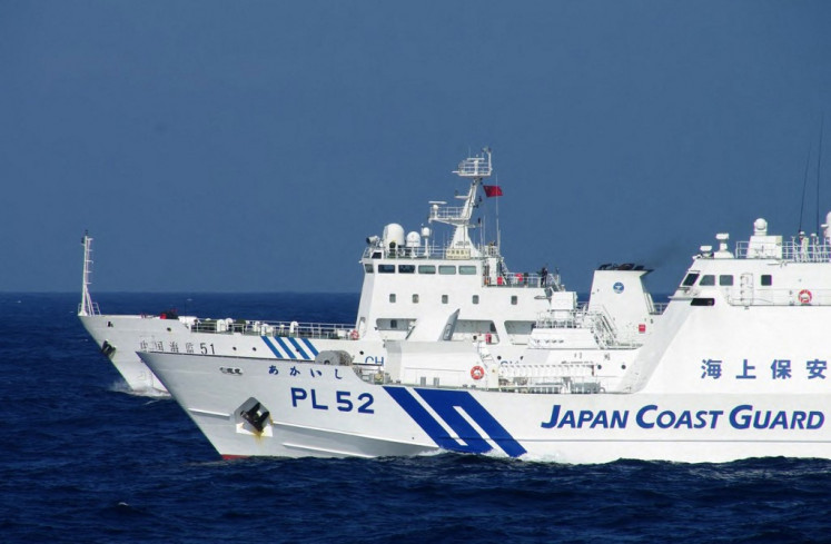 This handout picture taken by the Japan Coast Guard on February 4, 2013 shows a Chinese marine surveillance ship (back L) alongside a Japan Coast Guard ship near the disputed islets known as the Senkaku islands in Japan and Diaoyu islands in China, in the East China Sea. Two Chinese government ships on February 4 entered waters around the Tokyo-controlled islands that Beijing claims as it own. Beijing has repeatedly sent ships to the area since Japan nationalised some islands in the chain in September.