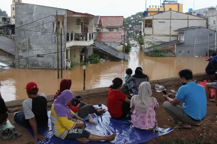 Flood-affected residents sit on higher ground in Jakarta on February 20, 2021, following heavy overnight rains.