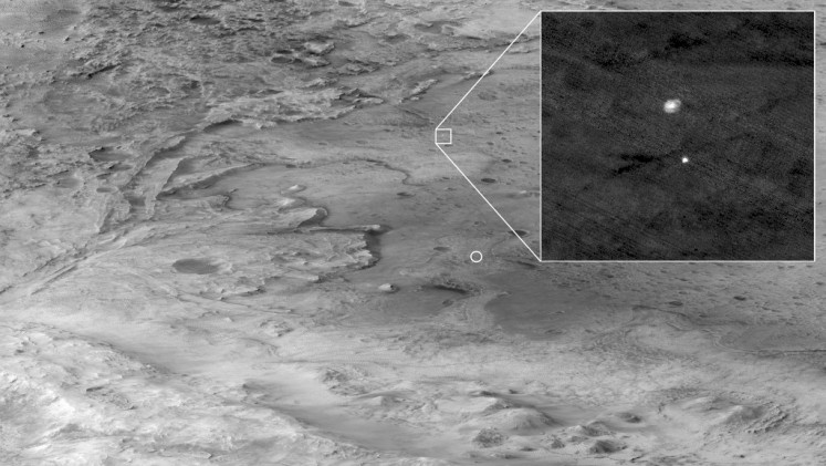 This NASA photo released on February 19, 2021, shows the descent stage of the Perseverance rover as it falls thorough the Martian atmosphere, its parachute trailing behind (inset), on February 18, 2021. The image was taken by the HiRISE camera aboard the Mars Reconnaissance Orbiter. The circle indicates where Perseverance eventually touched down within Jezero Crater. NASA said February 18, 2021 that the Perseverance had touched down on Mars after successfully overcoming a risky landing phase known as the