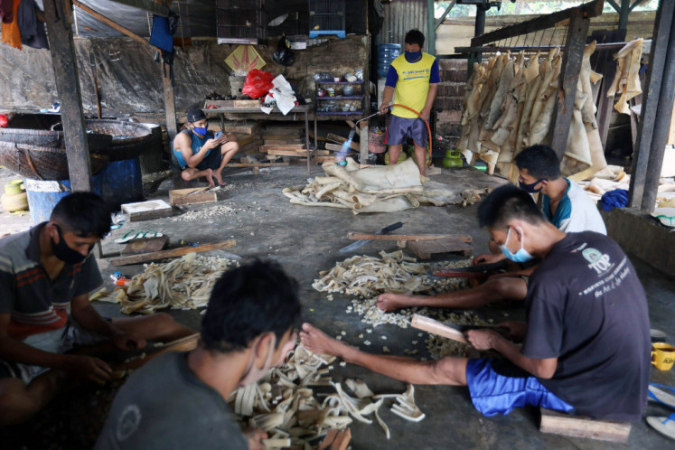 Workers remove the fine hairs on cowhide by burning it off before they cut them into small pieces to be used as ingredients for skin crackers at a home industry facility in Depok, West Java on Feb. 18, 2021. Home industries have suffered a hit in business due to the pandemic, although some still manage to hang on.