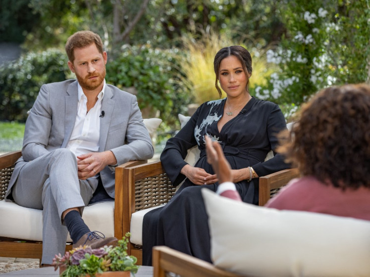 This undated image released March 7, 2021 courtesy of Harpo Productions shows Britain's Prince Harry (left) and his wife Meghan (center), Duchess of Sussex, in a conversation with US television host Oprah Winfrey.