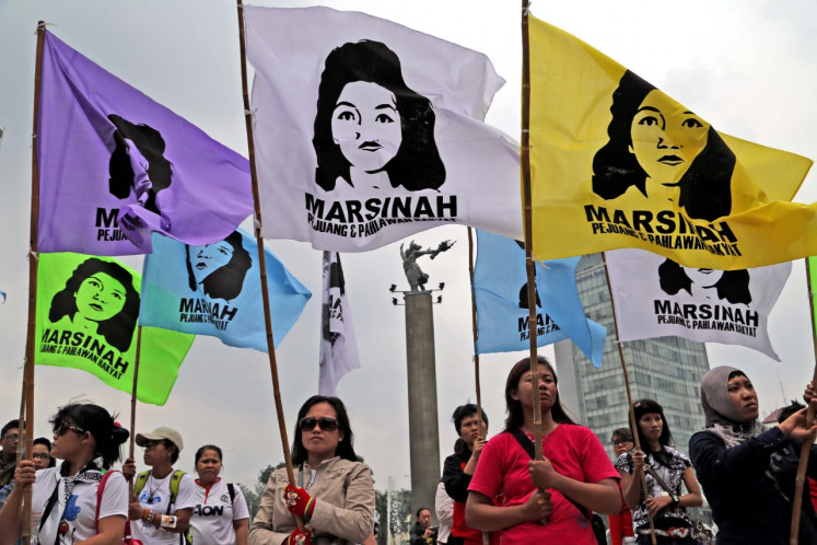 Pictures of Marsinah are shown during a labor protest at the Hotel Indonesia traffic circle in Central Jakarta on March 3, 2014. Marsinah was a factory worker who was killed in 1993 for demanding workers' rights, including the right for women to take menstrual leave.