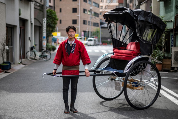 In this picture taken on March 12, 2021, rickshaw driver Yui Oikawa poses with a rickshaw, also known as the traditional Japanese two-wheeled passenger cart, in Taito district of Tokyo. Olympics organisers are expected to officially announce a ban on spectators from abroad in coming days, but those working in Japan's tourism industry have already resigned themselves to the inevitable.