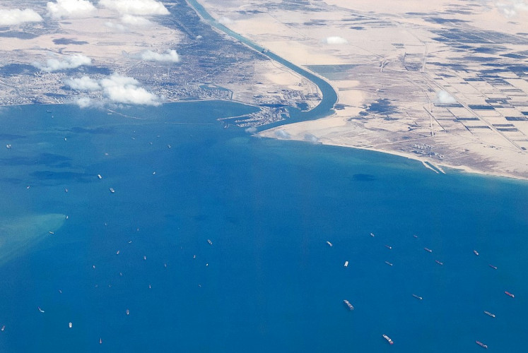 An aerial view taken on March 27, 2021 from the porthole of a commercial plane shows stranded ships waiting in queue in the Gulf of Suez to cross the Suez Canal at its southern entrance near the Red Sea port city of Suez, as the waterway remains blocked by the Panama-flagged container ship