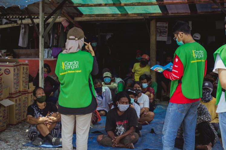 Anggota Carda Pangan memberi pengarahan kepada penduduk desa sebelum membagikan makanan.