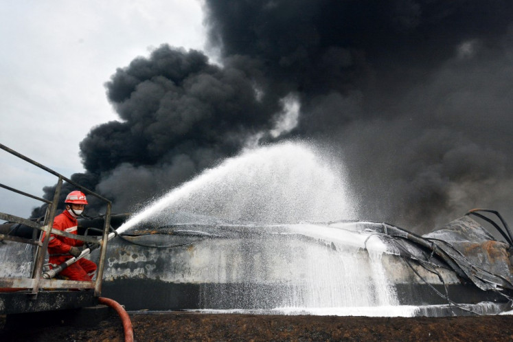 A firefighter battles a fire at Balongan refinery, operated by state oil company Pertamina, in Indramayu, West Java on March 31, 2021.